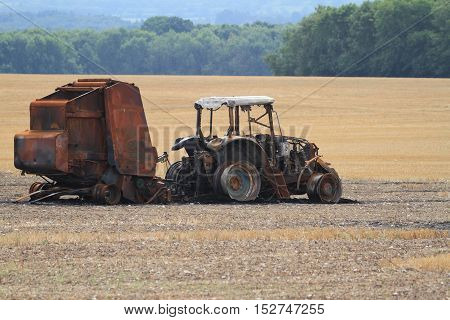 Tractor and hay bale machine burnt out in a field after the autumn harvest