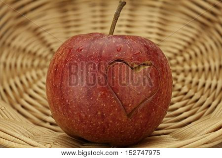 Red Apple with engraved heart in a basket