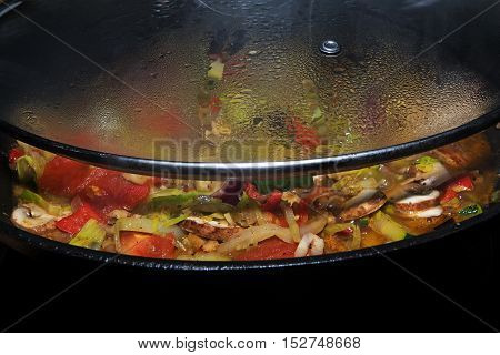 View under the half-open glass lid in a pot with boiling vegetables unusual perspective with copy space selected focus narrow depth of field