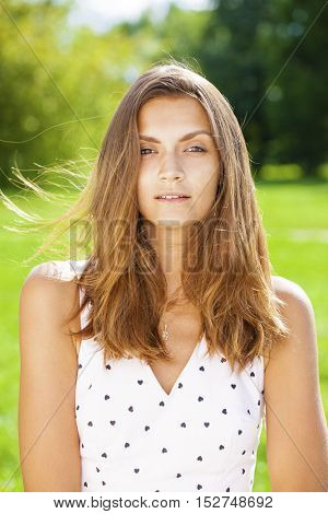 Close up portrait of beautiful young happy brunette woman in white dress, summer park outdoors