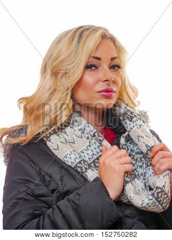 A attractive blond woman is wearing a winter coat in a studio setting.
