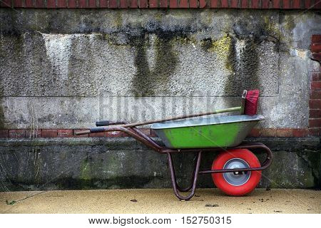 Green wheelbarrow with a red wheel and a red broom against a old weathered wall as a textured background with generous copy space