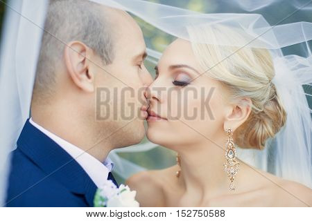 Amazing teen bride gently kisses the groom, close-up