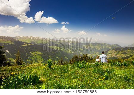 Father with his son enjoying view to Swiss Alps from the top of Madrisa mountain, Davos, Switzerland