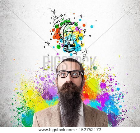 Baffled man in glasses with long beard is standing against concrete wall with colorful light bulb sketch. He is surrounded by rainbow splashes. Concept of creative idea