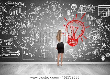 Rear view of blond woman drawing giant red light bulb sketch on blackboard with startup icons. Concept of excellent idea