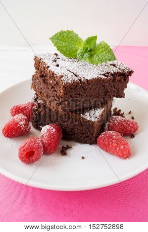 Sliced black bean brownie cake decorated with powdered sugar and mint and raspberry on on white plate selective focus vertical