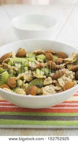 Whole grain cereal with kiwi and almond in white bowl and yogurt. Healthy breakfast. Health and diet concept selective focus close up vertical.