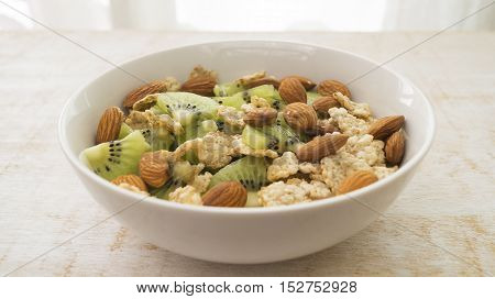 Whole grain cereal with kiwi and almond in white bowl. Healthy breakfast. Health and diet concept selective focus close up horizontal