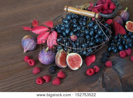 Black grapes in a basket and ripe figs red raspberries and blackberries with autumn leaves on the wooden background