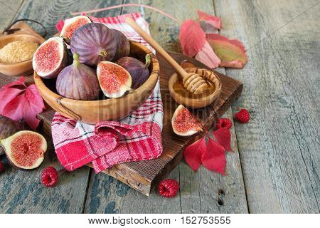 Ripe figs in a wooden bowl red raspberry cane sugar honey and a checkered napkin on old cutting board as well as autumn leaves lie on the old wooden table