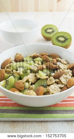 Whole grain cereal with kiwi and almond in white bowl and yogurt. Healthy breakfast. Health and diet concept selective focus close up.