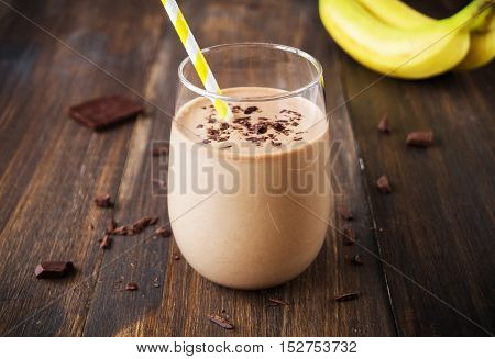 Chocolate banana smoothie in glass with paper straw on wooden background selective focus horizontal toned