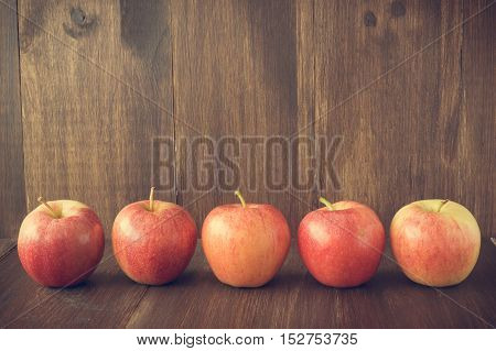 Apples on wooden rustic background. Autumn and harvest concept with copy space selective focus toned horizontal