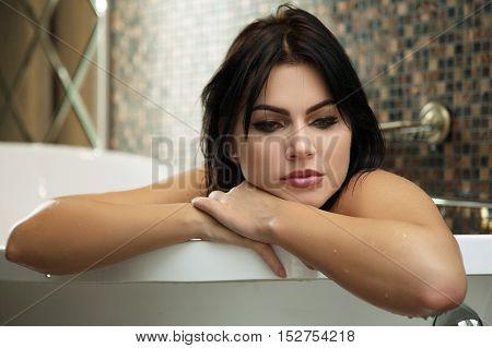 Beautiful sad brunette woman relaxing in bathtub