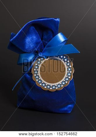 Small blue gift bag with ribbon and blank label on black background