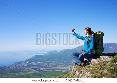 Happy young female traveller with backpack sitting at the edge of cliff at mountain landscape background in sunny summer day under blue cloudy sky with camera in hands and making selfy photo