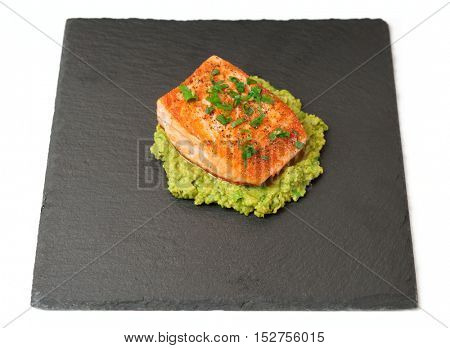 Grilled salmon fillet with avocado mash on black slate plate, isolated