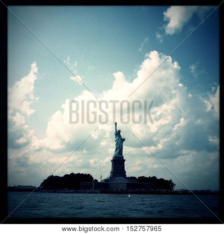 Vintage Filtered image of the Statue of Liberty in New York City with dramatic storm clouds