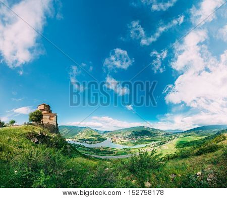 Mtskheta, Georgia. The Ancient Georgian Orthodox Church Of Holly Cross, Jvari Monastery With Remains Of Stone Wall, cenic Blue Cloudy Sky Background. World Heritage. Panorama