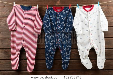 Baby boy clothes (sleepsuits) hanging on the clothesline