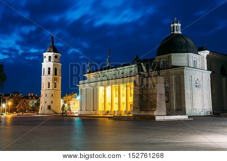 Vilnius, Lithuania. Night Or Evening View Of Cathedral Basilica Of St. Stanislaus And St. Vladislav With The Bell Tower, Blue Cloudy Sky Background. Catholic Cathedral At The Cathedral Square. Travel