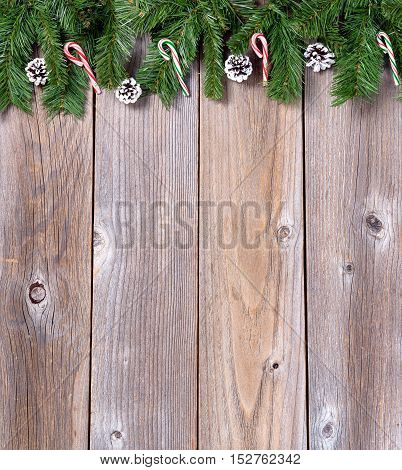 Christmas holiday wooden background with fir branches and candy canes.