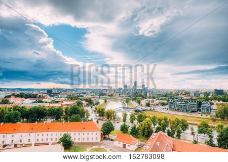 Vilnius, Lithuania. Top Scenic View Of Old And New Town With Neris River, Mindaugas Bridge Under Dramatic Cloudy Sky Of Summer Sunset Sunrise Dawn.