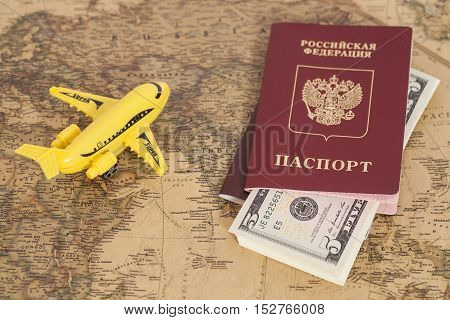 Model aircraft with Russian International passports and dollars on the world map background