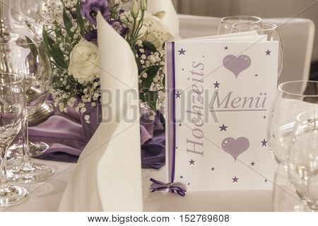 Wedding table with menu card napkins and flowers. High class arrangement for the lucky bride and groom on their big day.