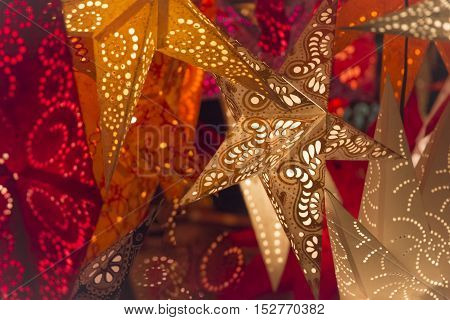 Colorful red golden orange xmas lantern stars christmas market. Shiny red orange golden stars at european christmas market. The colours of the best miracle time of the year. Part of series.