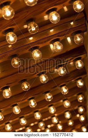 Plenty light bulbs shining bright. Many lightbulbs in rows on ceiling burn.