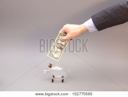 Male hand putting one dollar bill into glass piggy bank isolated on gray