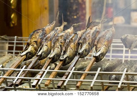 Barbecue stockfish grilled trout fish on stocks with fire smoke. Delicious crispy staple nutrition salmon at a medieval market with succulent flavor and protein.