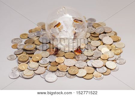 Glass piggy bank on coins isolated on gray