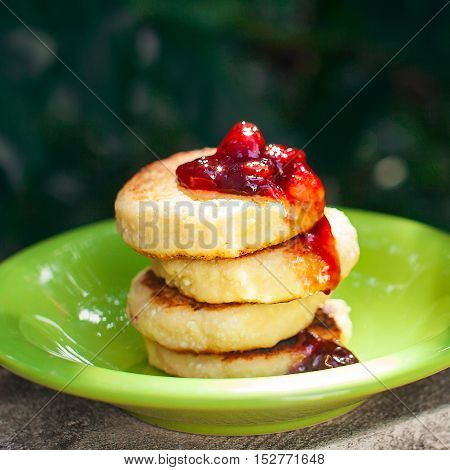 Sweet ricotta pancakes with cherry jam at the green plate on the nature background. Closeup selective focus.