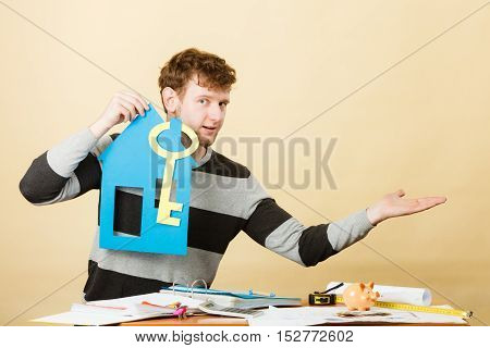 Good purchase concept. Male buyer with paper model of house and key. Smiling positive man buying his first real estate flat building.