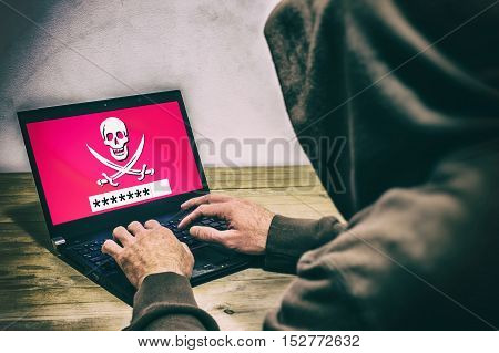Back View Of A Hacker Wearing A Hoodie And Stealing A Password On A Laptop Screen