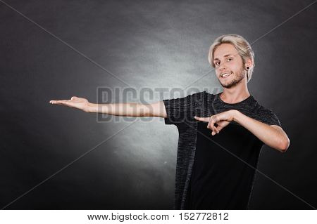 Young man showing presenting. Stylish guy pointion with finger holding empty hand palm copyspace for product. Fashion advertising concept. Studio shot on dark