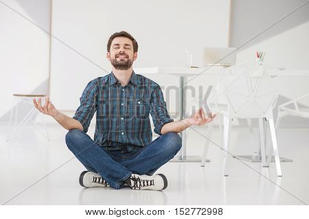 His favorite time of day. Smiling businessman sitting on floor cross legged and meditating at modern bright office indoors