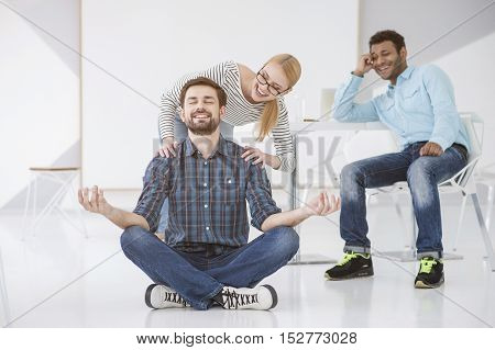 Yoga in the office. Smiling worker sitting on floor practicing yoga in lotus position with two colleague laughing at him in background