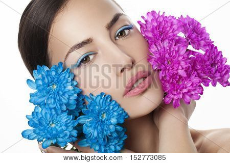 young woman beauty portrait with blue and pink flowers, studio white