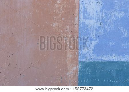 Image of a concrete wall in shades of blue and brown suitable for use as a background or texture.