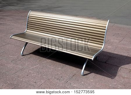Modern metal bench on street tile in the city in summer day side view