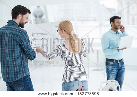 Working together for better results. Girl explaining her ideas about building to his male colleague, holding blueprint