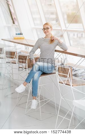 She keeping everyone smiling. Beautiful young woman sitting at her office desk on high chair near window in office