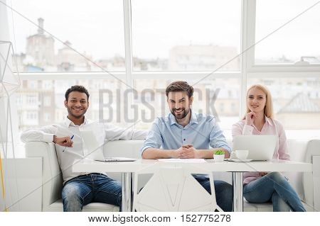 They are team you want. Three business colleagues having good time working together in their modern office