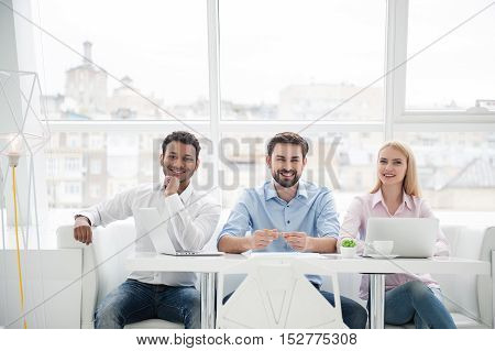 Positive and productive. Smiling young creative professionals working in modern office, sitting at desk