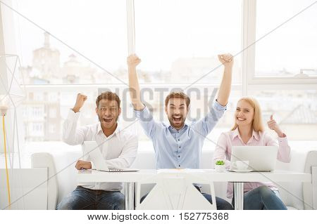 We made it. Cropped portrait of group of business people cheering in modern office