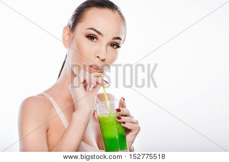 Confident slim woman is drinking kiwi juice with pleasure. She is standing and looking at camera with satisfaction. Isolated and copy space in right side